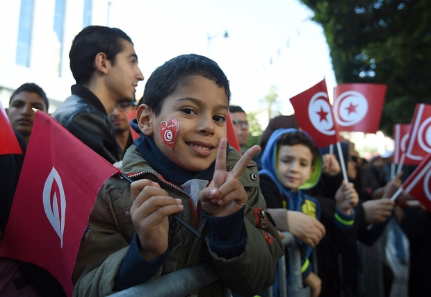 A Tunisian boy flahse the V-sign and holds his national flag during a rally on Habib Bourguiba Avenue in Tunis on January 14, 2016, to mark the fifth anniversary of the 2011 revolution. / AFP / FETHI BELAID